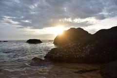Lever de soleil et roches de plage images libres de droits