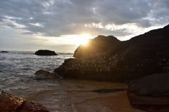 Lever de soleil et roches de plage photographie stock