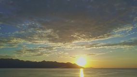 Lever de soleil fantastique au-dessus d'océan contre des collines avec le chemin de Sun