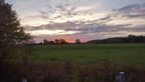 Lever de soleil orange au-dessus de champ Images libres de droits
