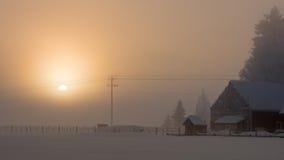 Lever de soleil par la ferme de famille d'hiver de brouillard image stock