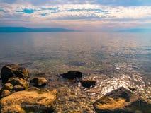 Lever de soleil peint dans les pierres de nuances d'or et d'émeraude et l'eau du Kinneret Photo libre de droits