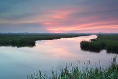 Lever de soleil pourpre au-dessus de rivière Image stock