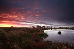 Lever de soleil pourpre dramatique au-dessus de rivière Image libre de droits