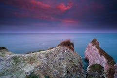 Lever de soleil rouge dramatique au-dessus des falaises dans l'océan Image stock