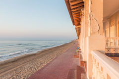 Lever de soleil sur de vieilles maisons sur le bord de mer d'une plage méditerranéenne Image stock