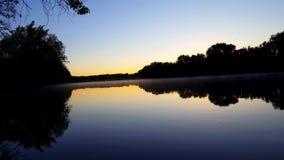 Lever de soleil sur l'horizon au-dessus de la brume débordante calme de rivière et de rivière de brume de matin entourée par la f clips vidéos