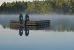 Lever de soleil sur la ligne d'arbre derrière le radeau sur le lac Photo libre de droits