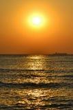 Lever de soleil sur la plage avec des vagues, un bateau sur l'horizon et voler de deux oiseaux Image stock