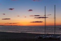 Lever de soleil sur la plage avec deux catamarans échoués sur le rivage à Mojacar Almeria Photos stock