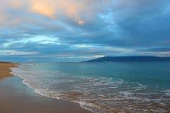 Lever de soleil sur la plage avec le rose nuageux et le Gray Sky et l'eau bleue Image stock