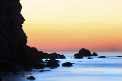 Lever de soleil sur la plage avec les roches et la mer Image stock