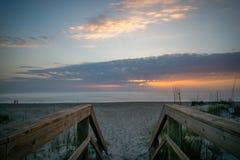 Lever de soleil sur la plage du passage couvert photos stock