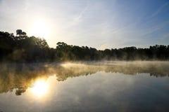 Lever de soleil sur le lac avec la brume en hausse photo stock