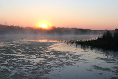 Lever de soleil sur le lac couvert de brouillard Images libres de droits