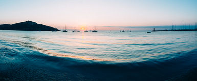 Lever de soleil sur une petite baie avec les voiliers ancrés Photographie stock