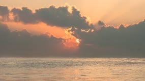Lever de soleil vibrant au-dessus de la mer avec des nuages et des rayons de soleil Images stock
