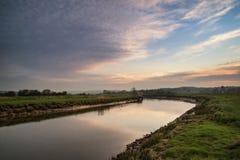 Lever de soleil vibrant renversant reflété en rivière calme photos stock
