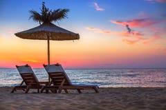 Lever de soleil vif sur une belle plage sablonneuse avec le parasol photo stock