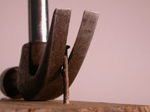 Leverage. A claw hammer pulls up an old rusty nail Royalty Free Stock Image
