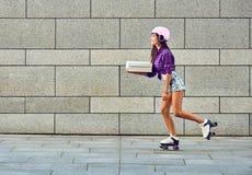 Leverans på rullskridskor av den härliga flickan i hjälm fotografering för bildbyråer