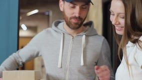 Leverans, post, folk och sändningsbegrepp - lycklig man som levererar jordlottaskar till kundhemmet Ge skrivplattan för lager videofilmer