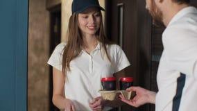 Leverans-, post- och folkbegrepp - lycklig kvinna som levererar kaffe och mat i disponibel pappers- påse till kundhemmet och stock video