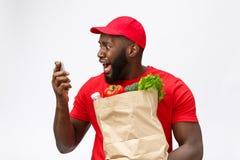 Leveransbegrepp: Stilig afrikansk pizzaleveransman som talar till mobilt med chockerande ansiktsuttryck Isolerat över royaltyfria bilder