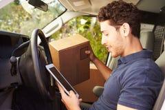 Leveranschaufför Sitting In Van Using Digital Tablet royaltyfria foton