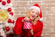 Leveransjulgåvor Lycklig flicka i den Santa Claus hatten Le kvinnan som firar jul Parti för nytt år glatt royaltyfri bild