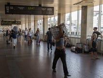 Leveransmän som bär skurkrolljordlotter, packar och bagage i avvikelselobbyen av den Kiev järnvägsstationen arkivbilder