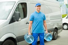 Leveransman med två stora vattenflaskor Arkivbilder