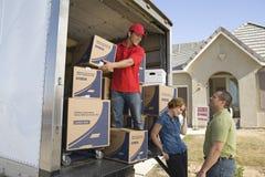 Leveransman och par som lastar av flyttande askar från lastbilen Arkivfoton