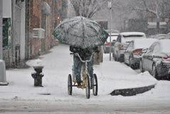 leveransman, på cykeln i snöstorm royaltyfria bilder