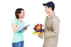 Leveransman som tar häftet av kvinnan, medan att leverera blommar Royaltyfri Bild