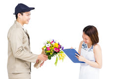 Leveransman som tar häftet av kvinnan, medan att leverera blommar Royaltyfri Foto