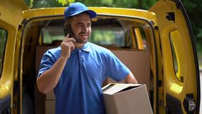 Leveransmannen i blå likformig rymmer en kartong, medan tala på telefonen stock video