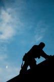 Leverantör i konturn som arbetar på en taköverkant Royaltyfria Bilder