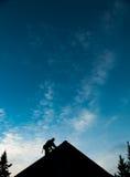 Leverantör i konturn som arbetar på en taköverkant Fotografering för Bildbyråer