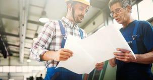 Leverantör med teknikern som kontrollerar på produktion i fabrik arkivfoton