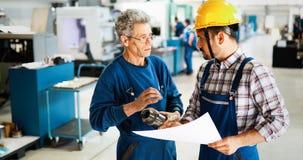 Leverantör med teknikern som kontrollerar på produktion i fabrik arkivbilder