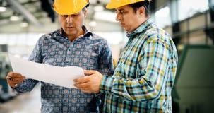 Leverantör med teknikern som kontrollerar på produktion i fabrik royaltyfria foton
