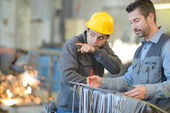 Leverantör med teknikern som kontrollerar på produktion i fabrik arkivbild