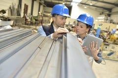Leverantör med teknikern som kontrollerar på produktion i metallurgisk fabrik royaltyfri foto