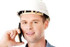 Leverantören i hardhat talar på hans mobiltelefon royaltyfria bilder