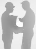 Leverantören och iscensätter att diskutera en planera, silhouettes Fotografering för Bildbyråer