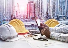 Leverantörman som arbetar på kontorstabellen mot projekt för konstruktionsplats royaltyfria bilder