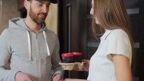 Levering, post en mensenconcept - gelukkige mens die koffie en voedsel in beschikbare document zak leveren aan klantenhuis en stock video
