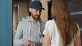 Levering, post en mensenconcept - gelukkige mens die koffie en voedsel in beschikbare document zak leveren aan klantenhuis en stock footage