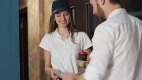 Levering, post en mensenconcept - gelukkige vrouw die koffie en voedsel in beschikbare document zak levert aan klantenhuis en stock video